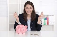 Νέα όμορφα χρήματα αρίθμησης επιχειρησιακών γυναικών - νομίσματα με μια piggy απαγόρευση Στοκ εικόνες με δικαίωμα ελεύθερης χρήσης