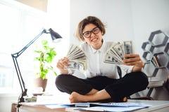 Νέα όμορφα χρήματα εκμετάλλευσης επιχειρηματιών, συνεδρίαση στον πίνακα στον εργασιακό χώρο Στοκ εικόνες με δικαίωμα ελεύθερης χρήσης