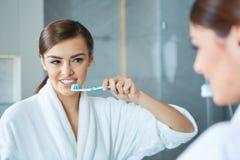Νέα όμορφα δόντια βουρτσίσματος γυναικών Στοκ φωτογραφία με δικαίωμα ελεύθερης χρήσης