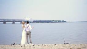 Νέα όμορφα newlyweds που στέκονται στην παραλία, με τα ποτήρια της σαμπάνιας και κάτω από μια διαφανή ομπρέλα, ενάντια φιλμ μικρού μήκους