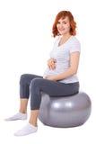 Νέα όμορφη έγκυος γυναίκα που κάνει τις ασκήσεις στο fitball που απομονώνεται Στοκ Εικόνα