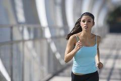Νέα όμορφη αθλητικός αθλήτρια που τρέχει και που διασχίζοντας τη σύγχρονη γέφυρα πόλεων μετάλλων Στοκ Φωτογραφία