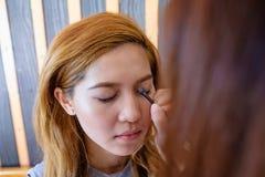 Νέα όμορφη ασιατική γυναίκα που εφαρμόζει τη σύνθεση Στοκ Φωτογραφίες