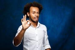 Νέα όμορφη αφρικανική παρουσίαση ατόμων εντάξει, κλείνοντας το μάτι πέρα από το μπλε υπόβαθρο Στοκ Φωτογραφία