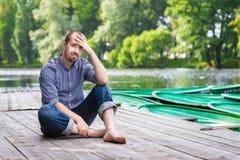 Νέα όμορφη γενειοφόρος συνεδρίαση ατόμων στην ξύλινη αποβάθρα στη θερινή ημέρα Στοκ φωτογραφία με δικαίωμα ελεύθερης χρήσης