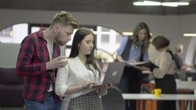 Νέα όμορφη γυναίκα και γενειοφόρος άνδρας που συζητούν τη στάση προγράμματος στο γραφείο με το netbook στα χέρια Το θηλυκό τους απόθεμα βίντεο