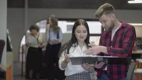 Νέα όμορφη γυναίκα και γενειοφόρος άνδρας που συζητούν τη στάση προγράμματος στο γραφείο με το μεγάλο φάκελλο εγγράφου Το θηλυκό  απόθεμα βίντεο