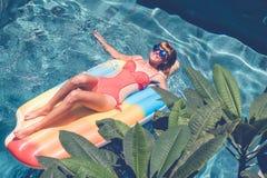 Νέα όμορφη γυναίκα με τέλειο μαυρισμένο να βρεθεί σωμάτων στο στρώμα αέρα στη λίμνη το καλοκαίρι και την κατοχή της διασκέδασης Χ Στοκ φωτογραφία με δικαίωμα ελεύθερης χρήσης
