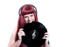 Νέα όμορφη γυναίκα με τα ακουστικά που δαγκώνουν το βινυλίου δίσκο Στοκ φωτογραφία με δικαίωμα ελεύθερης χρήσης
