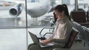 Νέα όμορφη γυναίκα με τα ακουστικά στα αυτιά που τυπώνουν στη συνεδρίαση lap-top στον αερολιμένα απόθεμα βίντεο