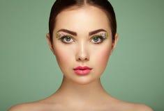 Νέα όμορφη γυναίκα με τα μάτια λουλουδιών makeup στοκ εικόνες