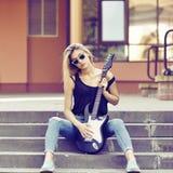 Νέα όμορφη γυναίκα με την ηλεκτρική κιθάρα που φορά τα γυαλιά ηλίου Στοκ Εικόνες