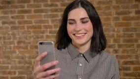 Νέα όμορφη γυναίκα με την κοντή καφετιά τρίχα που εξετάζει το τηλέφωνο και που γελά, υπόβαθρο τουβλότοιχος φιλμ μικρού μήκους