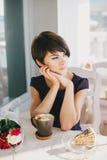 Νέα όμορφη γυναίκα με την κοντή τρίχα που πίνει βράζοντας τον καφέ στον ατμό Στοκ Φωτογραφία