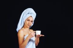 Νέα όμορφη γυναίκα με την πετσέτα στο επικεφαλής υπόβαθρο φλυτζανιών Στοκ Εικόνες