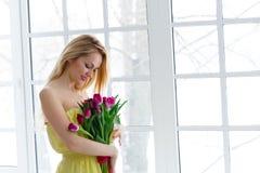 Νέα όμορφη γυναίκα με τη δέσμη τουλιπών στο κίτρινο φόρεμα 8 Μαρτίου ημέρα των διεθνών γυναικών στοκ εικόνα