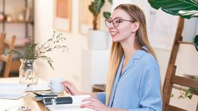 Νέα όμορφη γυναίκα με τη μακριά ατημέλητη τρίχα, που φορά τα γυαλιά, που λειτουργούν στο γραφείο, ευτυχές χαμόγελο στοκ εικόνα με δικαίωμα ελεύθερης χρήσης