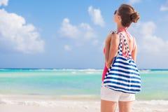 Νέα όμορφη γυναίκα με τη ρηγέ τσάντα σε ηλιόλουστο Στοκ φωτογραφία με δικαίωμα ελεύθερης χρήσης
