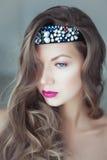 Νέα όμορφη γυναίκα με τη στεφάνη στην τρίχα και τα μπλε μάτια στοκ φωτογραφία