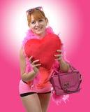 Νέα όμορφη γυναίκα με το μεγάλο κόκκινο μαξιλάρι καρδιών Στοκ Εικόνες
