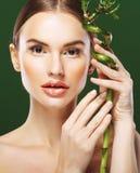 Νέα όμορφη γυναίκα με το μπαμπού πέρα από το πράσινο υπόβαθρο Στοκ φωτογραφία με δικαίωμα ελεύθερης χρήσης