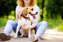Νέα όμορφη γυναίκα με το σκυλί λαγωνικών στο πάρκο Στοκ Εικόνες