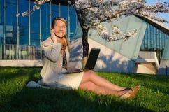 Νέα όμορφη γυναίκα με το τηλέφωνο και το lap-top Στοκ εικόνα με δικαίωμα ελεύθερης χρήσης