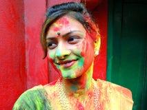 Νέα όμορφη γυναίκα με το χρωματισμένο πρόσωπο που γιορτάζει Holi Στοκ εικόνα με δικαίωμα ελεύθερης χρήσης