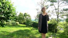 Νέα όμορφη γυναίκα μόδας που περπατά σε ένα πάρκο, θερινός χρόνος απόθεμα βίντεο