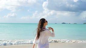 Νέα όμορφη γυναίκα που έχει τη διασκέδαση στην τροπική ακτή Ευτυχές κορίτσι που περπατά στην άσπρη τροπική παραλία άμμου κίνηση α απόθεμα βίντεο