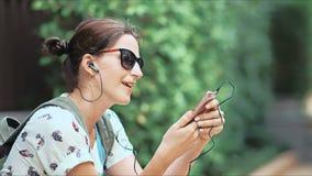 Νέα όμορφη γυναίκα που ακούει τη μουσική, που χορεύει και που τραγουδά στο πάρκο απόθεμα βίντεο