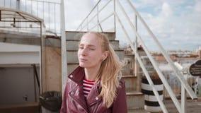 Νέα όμορφη γυναίκα που απολαμβάνει το χρόνο σε μια στέγη Ο περίπατος κάτω από τα σκαλοπάτια και εξετάζει τη κάμερα με το χαμόγελο απόθεμα βίντεο