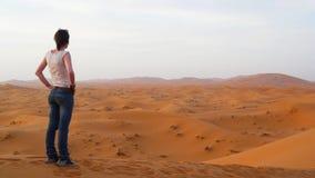 Νέα όμορφη γυναίκα που απολαμβάνει μια καταπληκτική θέα πέρα από την κόκκινη θάλασσα αμμόλοφων Erg Chebbi, με την καμήλα bedouins Στοκ Φωτογραφία