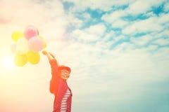 Νέα όμορφη γυναίκα που απολαμβάνει τα πολύχρωμα μπαλόνια στο brig Στοκ Εικόνες