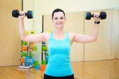 Νέα όμορφη γυναίκα που ασκεί με τους αλτήρες στη γυμναστική Στοκ Εικόνα