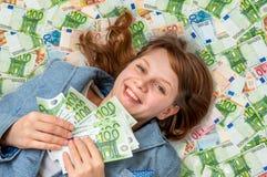 Νέα όμορφη γυναίκα που βρίσκεται στο ευρο- υπόβαθρο χρημάτων Στοκ Φωτογραφία