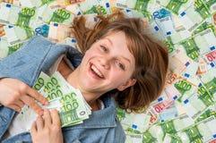 Νέα όμορφη γυναίκα που βρίσκεται στο ευρο- υπόβαθρο χρημάτων Στοκ Εικόνες