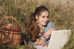 Νέα όμορφη γυναίκα που βρίσκεται στο πεδίο στο lap-top Στοκ Εικόνες