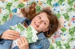 Νέα όμορφη γυναίκα που βρίσκεται στο υπόβαθρο χρημάτων Στοκ φωτογραφία με δικαίωμα ελεύθερης χρήσης