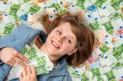 Νέα όμορφη γυναίκα που βρίσκεται στο υπόβαθρο χρημάτων Στοκ Εικόνα