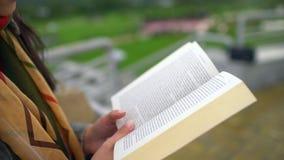 Νέα όμορφη γυναίκα που διαβάζει μια συνεδρίαση βιβλίων σε έναν πάγκο έξω σε ένα πάρκο το καλοκαίρι στενός επάνω βιβλίων 4 Κ απόθεμα βίντεο