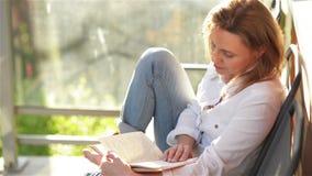 Νέα όμορφη γυναίκα που διαβάζει το ενδιαφέρον βιβλίο στο πεζούλι, κατά τη διάρκεια της ηλιόλουστης ημέρας απόθεμα βίντεο
