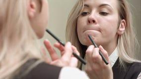 Νέα όμορφη γυναίκα που εφαρμόζει το κόκκινο κραγιόν στα χείλια της απόθεμα βίντεο