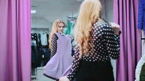 Νέα, όμορφη γυναίκα που ελέγχει την εμφάνισή της μπροστά από τον καθρέφτη απόθεμα βίντεο