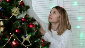 Νέα όμορφη γυναίκα που διακοσμεί το χριστουγεννιάτικο δέντρο φιλμ μικρού μήκους