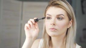 Νέα όμορφη γυναίκα που ισχύει makeup στο βλέφαρο με τη βούρτσα απόθεμα βίντεο