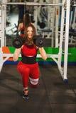 Νέα όμορφη γυναίκα που κάνει τις ασκήσεις με τον αλτήρα στη γυμναστική Το ευτυχές χαμογελώντας κορίτσι απολαμβάνει με τη διαδικασ στοκ εικόνα