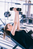 Νέα όμορφη γυναίκα που κάνει τις ασκήσεις με τον αλτήρα στη γυμναστική Στοκ Εικόνα