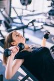 Νέα όμορφη γυναίκα που κάνει τις ασκήσεις με τον αλτήρα στη γυμναστική Στοκ εικόνες με δικαίωμα ελεύθερης χρήσης