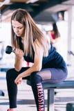 Νέα όμορφη γυναίκα που κάνει τις ασκήσεις με τον αλτήρα στη γυμναστική Στοκ Εικόνες